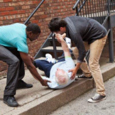 Two young men helping fallen senior