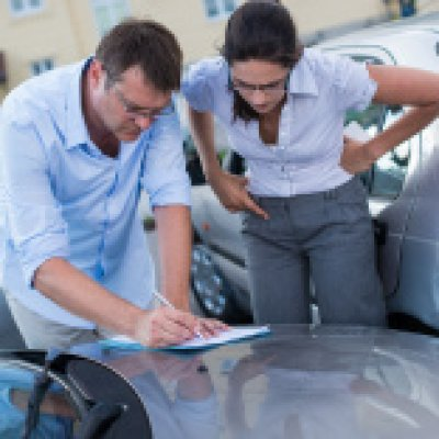 Man and woman filling out car accident report
